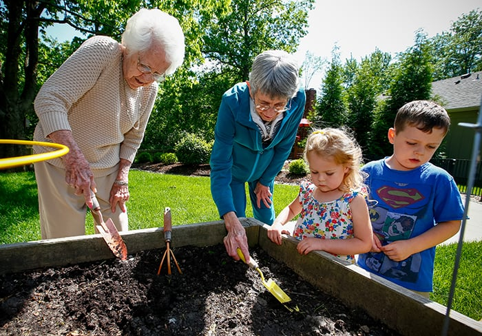 senior ladies and 2 children gardening