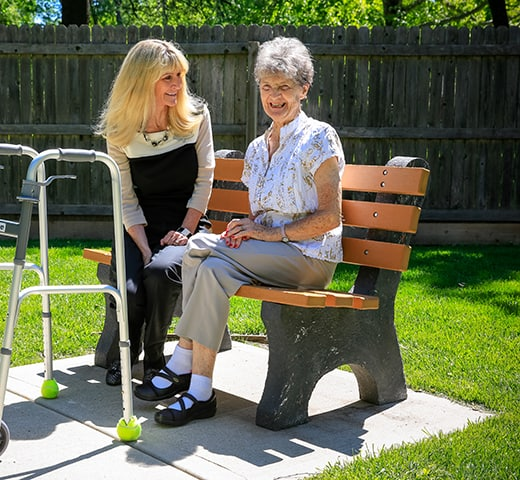 senior woman on bench with staff member